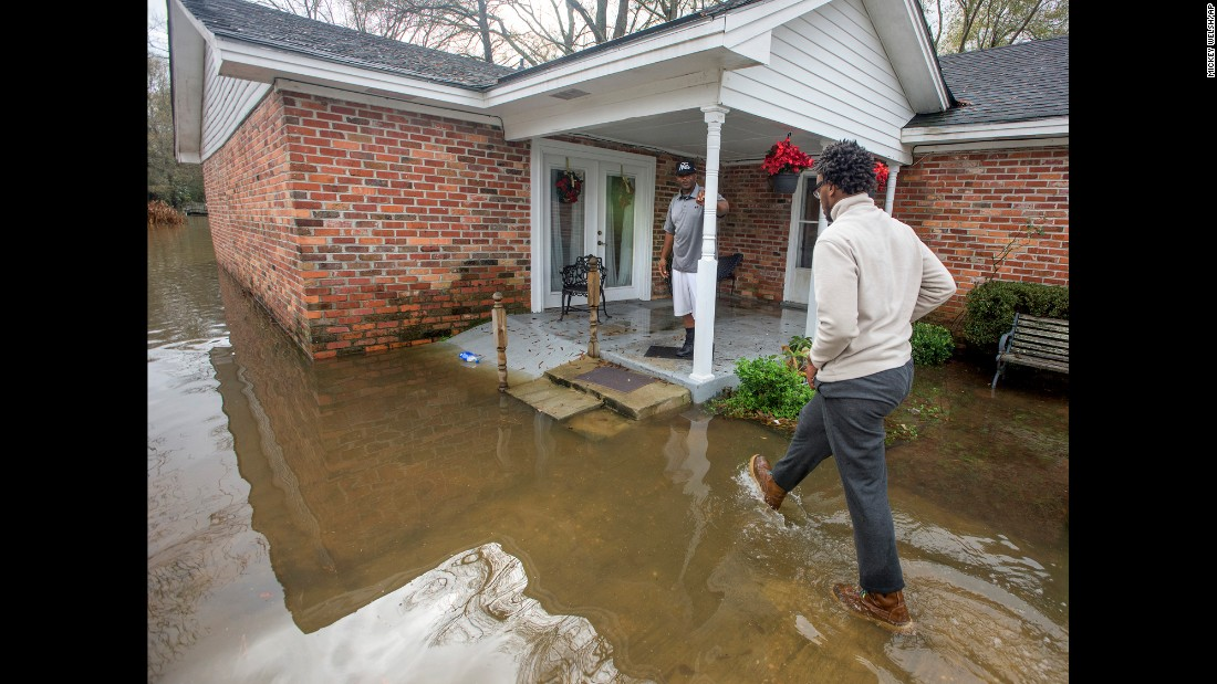 Gregory Shuford, left, and Terease Shuford check out the flooding in their west Montgomery, Alabama, neighborhood, on Christmas morning Friday, December 25. The line of severe storms continued marching eastward, dumping torrential rain that flooded roads in Alabama and caused a mudslide in the mountains of Georgia.