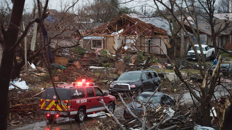 An emergency vehicle drives through a neighborhood in Rowlett, Texas. Crews were busy Sunday, December 27, scouring debris for victims and assessing the damage in North Texas after deadly storms spawned tornadoes that ripped through Dallas suburbs Saturday evening.
