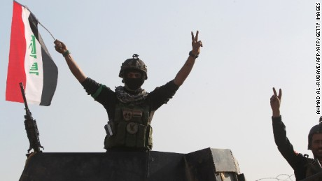 """Members of Iraq's elite counter-terrorism service flash the """"V"""" for victory sign on December 28, 2015 at the heavily damaged government complex after they recaptured the city of Ramadi, the capital of Iraq's Anbar province, about 110 kilometers west of Baghdad, from Islamic States group jihadists. Iraq declared the city of Ramadi liberated from the Islamic State group and raised the national flag over its government complex after clinching a landmark victory against the jihadists. AFP PHOTO / AHMAD AL-RUBAYEAHMAD AL-RUBAYE/AFP/Getty Images"""