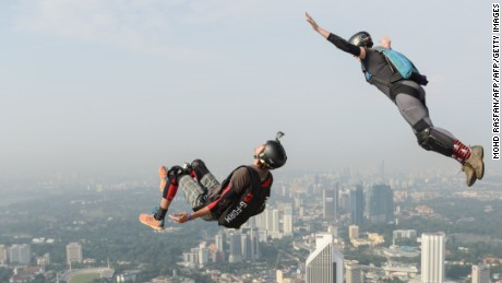 Base jumpers Annette O'Neil (top) and Bret Kistler (bottom) of the US leap from the 300-metre high Open Deck of Malaysia's landmark Kuala Lumpur Tower during the International Tower Jump in Kuala Lumpur on September 27, 2014. Some 100 professional base jumpers from 20 countries are taking part in the annual event. AFP PHOTO / MOHD RASFAN        (Photo credit should read MOHD RASFAN/AFP/Getty Images)