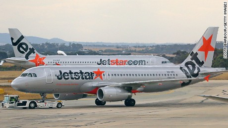 MELBOURNE, AUSTRALIA - FEBRUARY 25: A Jetstar aeroplane prepares to take off as Qantas aeroplanes wait at Melbourne Tullamarine Airport on February 25, 2014 in Melbourne, Australia. On Thursday Qantas will announce their half year results, media reports suggest part of those announcements will include a large number of job cuts and the sale of their Melbourne terminal. (Photo by Scott Barbour/Getty Images)