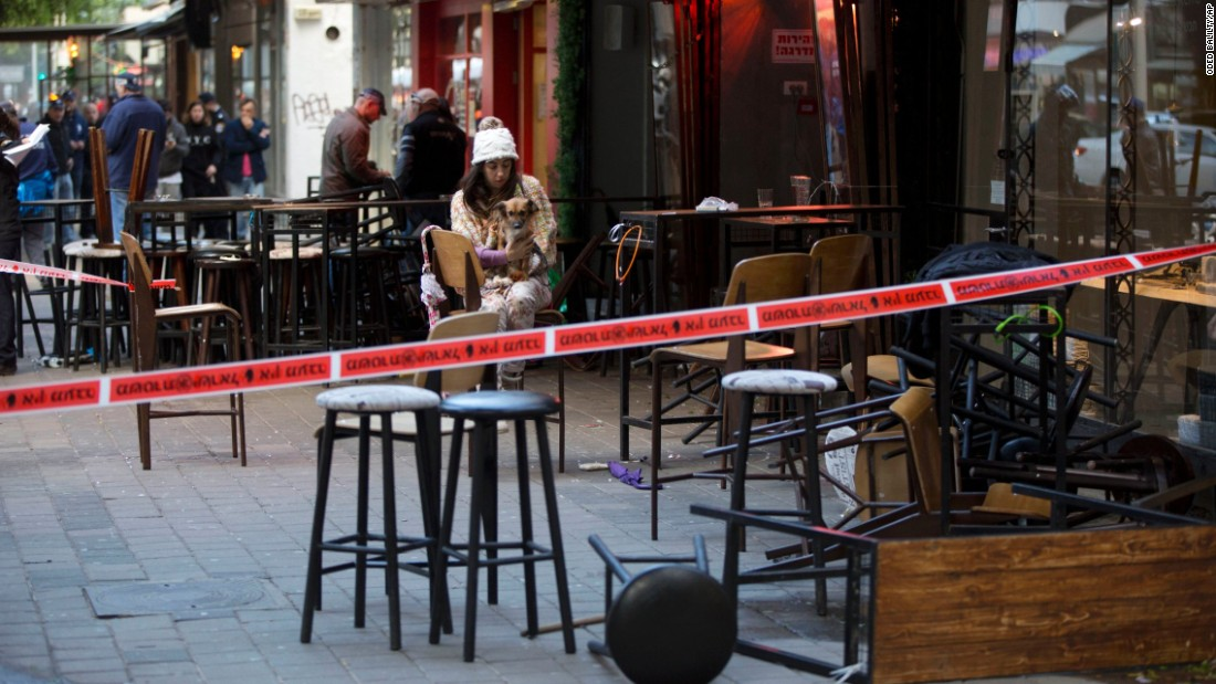 """An eyewitness sits with her dog at the scene of <a href=""""http://www.cnn.com/2016/01/01/middleeast/tel-aviv-pub-shooting/index.html"""" target=""""_blank"""">a shooting in Tel Aviv, Israel,</a> on Friday, January 1. At least two people were killed and four were injured when an unidentified gunman opened fire on a group of people near a pub, authorities said."""