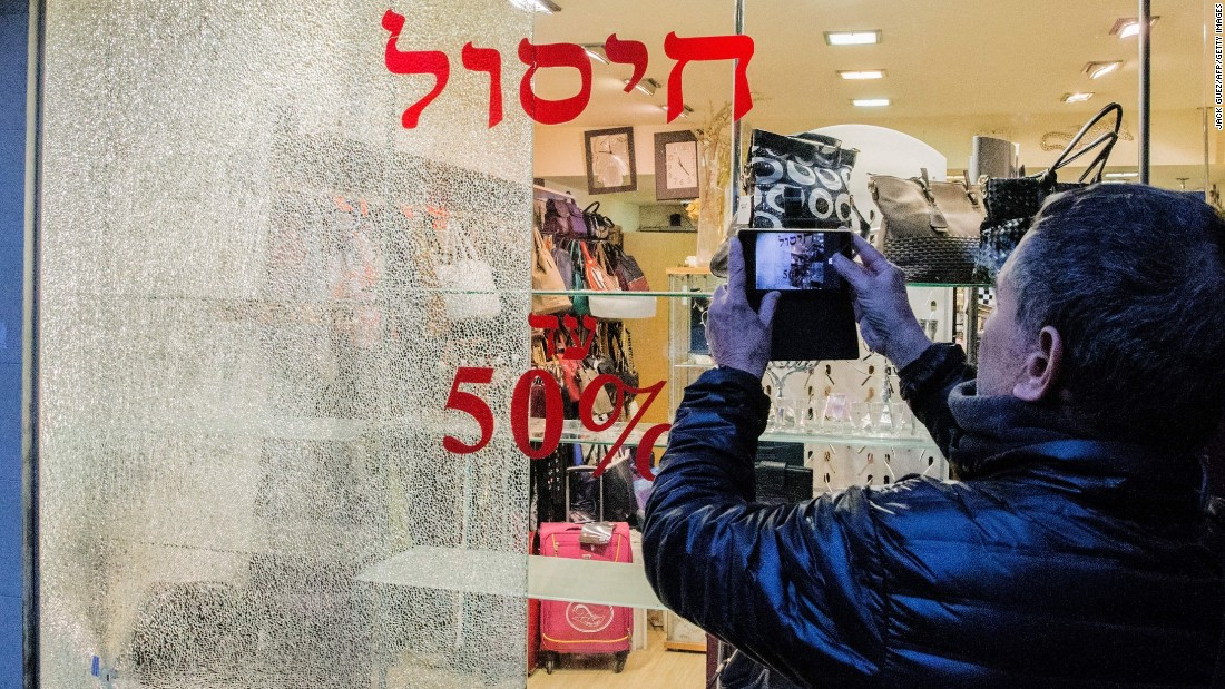 A man takes pictures of a broken shop window.