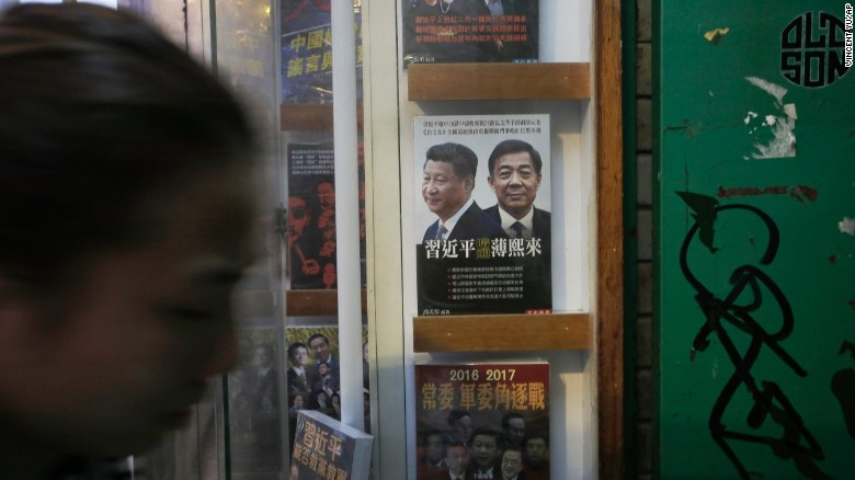 A woman walks past a book featuring a photo of Chinese President Xi Jinping, left, and former Politburo member and Chongqing city party leader Bo Xilai on the cover, at the entrance of the closed Causeway Bay Bookstore, Sunday, January 3, 2016.