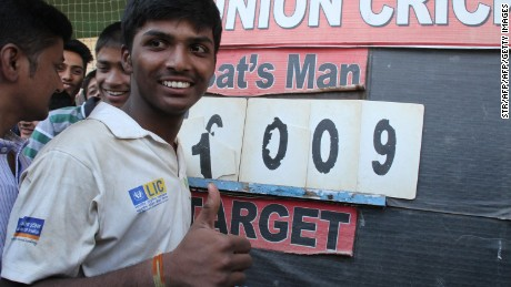 Mumbai schoolboy Pranav Dhanawade, 15, poses next to the score board after smashing a 117-year-old record for the highest number of runs scored in one innings in Mumbai on January 5, 2016. A Mumbai schoolboy made history on January 5 when he became the first batsman in any class of cricket to score 1,000 runs in a single innings, with Indian legend Sachin Tendulkar leading the plaudits.  Dhanawade smashed his way to 1,009 not out off 323 balls.   AFP PHOTO / AFP / STR        (Photo credit should read STR/AFP/Getty Images)