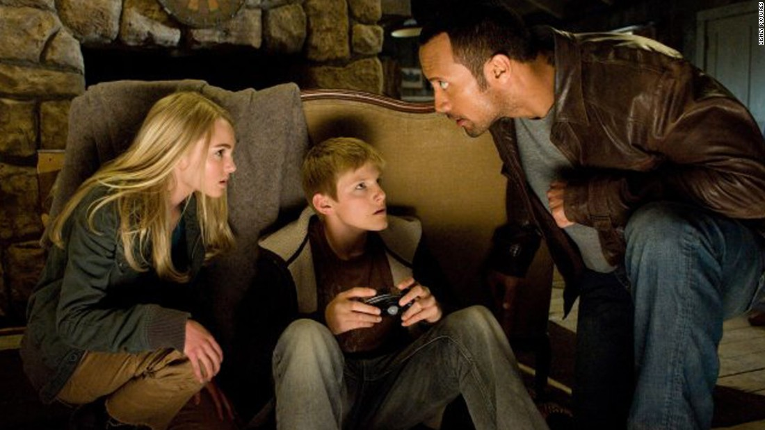 """Johnson has successfully mixed action flicks with Disney movies such as the 2009 remake of """"Race to Witch Mountain,"""" here with AnnaSophia Robb and Alexander Ludwig. His cab driver role even sparked a meme."""