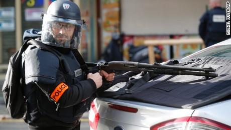 A police officer takes position after a fatal shooting which took place at a police station in Paris, Thursday, Jan. 7, 2016. Officers shot and killed a knife-wielding man with wires protruding from his clothes at a police station in northern Paris on Thursday, French officials said, a year to the day after an attack on the French satirical newspaper Charlie Hebdo launched a bloody year in the French capital. (AP Photo/Michel Euler)