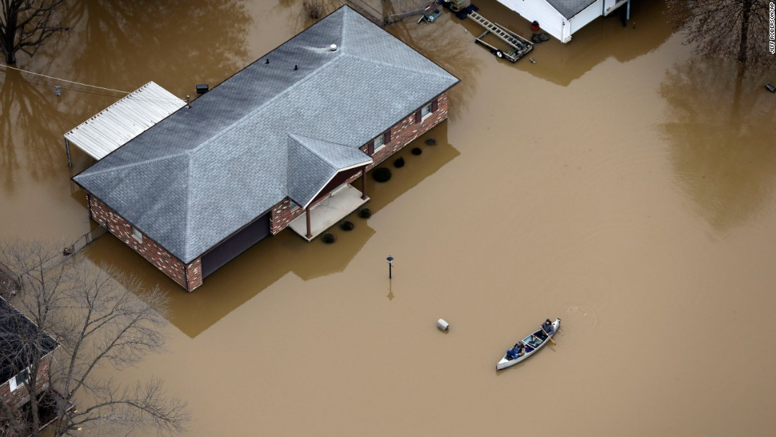 In this aerial photo, people use a canoe to navigate a flooded street on December 31 in Arnold, Missouri. Up to a foot of rain fell in parts of Missouri and Illinois, surging the Mississippi River and many of its tributaries to record levels. As many as 13 people died in Missouri alone and hundreds more were evacuated as the flooding threatened dozens of levees, many in the St. Louis area.