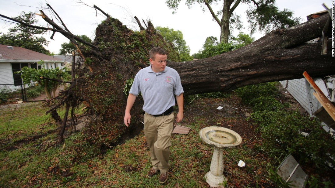 James Lucas, the public information officer for Marion County Fire Rescue, walks past a large oak tree that went through a home during severe weather in Ocala, Florida, on April 20. Nearly 40 tornadoes occurred from April 18-20 in 11 states across the South and Southeast.