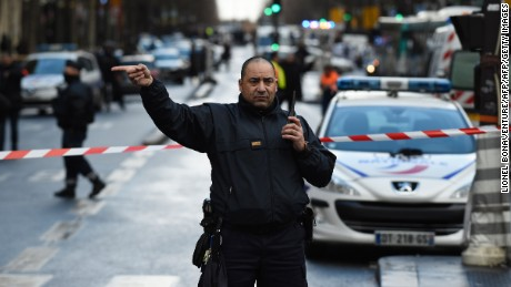 "A French police officer redirects traffic at the Boulevard de Barbes in the north of Paris on January 7, 2016, after police shot a man dead as he was trying to enter a police station in the Rue de la Goutte d'Or. A witness told AFP he had heard ""two or three shots"" in the incident that occurred a year to the day of the jihadist attack on satirical newspaper Charlie Hebdo. The man attempting to attack the police station cried 'Allahu Akbar', was armed with a knife and wore an apparent explosives vest. AFP PHOTO / LIONEL BONAVENTURE / AFP / LIONEL BONAVENTURE        (Photo credit should read LIONEL BONAVENTURE/AFP/Getty Images)"