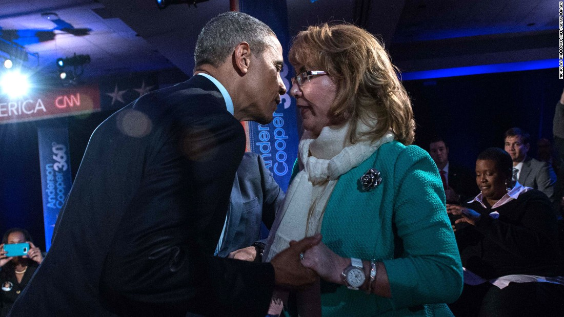 Obama greets former U.S. Rep. Gabby Giffords during a commercial break. Giffords was shot in an assassination attempt in 2011.