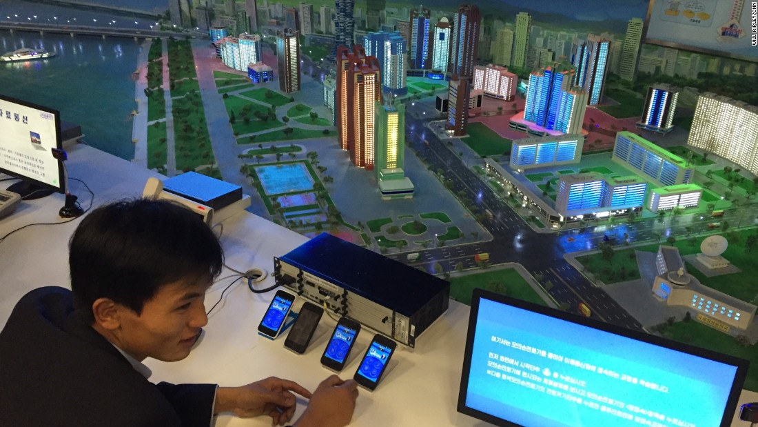 A guide shows visitors a display in the North Korean Science and Technology Center.