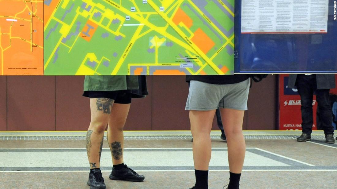 Two men wait for a train in their underwear in Warsaw, Poland.