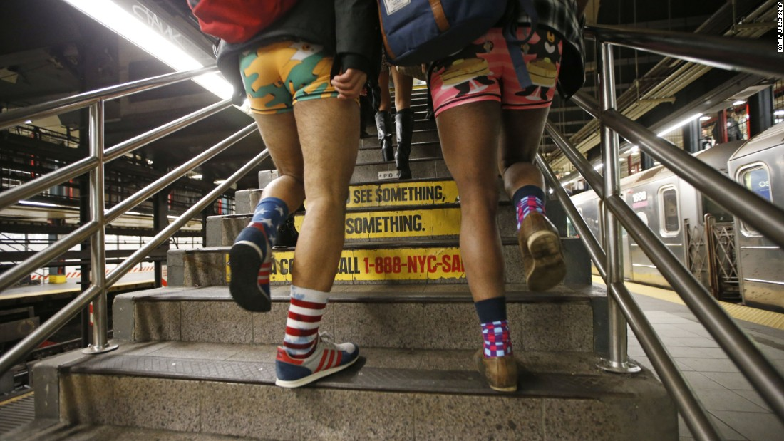 Two men clad in colorful underwear walk up subway steps in New York.