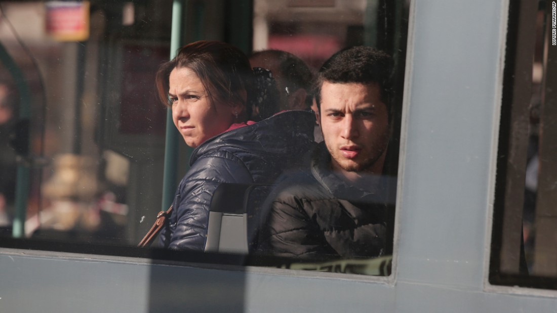 People on a tram look out the window as it drives past the tourism hub where the explosion occurred.