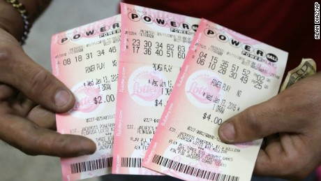 A customer shows his purchased Powerball tickets at a grocery store in Hialeah, Fla., Monday, Jan. 11, 2016. The Powerball jackpot has grown to over 1 billion dollars. (AP Photo/Alan Diaz)