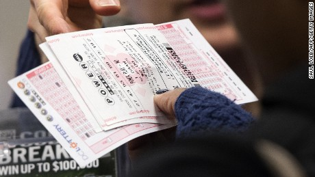A woman purchases a Powerball lottery ticket at a convenience store in Washington, DC, January 7, 2016. Lottery officials predict Saturday's jackpot will reach $700 million, the largest in history. AFP PHOTO / SAUL LOEB / AFP / SAUL LOEB        (Photo credit should read SAUL LOEB/AFP/Getty Images)