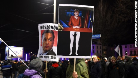 "Protesters in Leipzig hold aloft posters depicting German Chancellor Angela Merkel being groped and of Hungarian PM Viktor Orban, known for his anti-migrant stance. The latter reads ""Thanks"" in Hungarian."