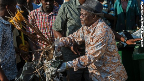 Tanzanian President John Magufuli joins a clean-up event outside the State House in Dar es Salaam on December 9, 2015. Magufuli cancelled Independence Day celebrations and ordered a national day of clean-up instead.