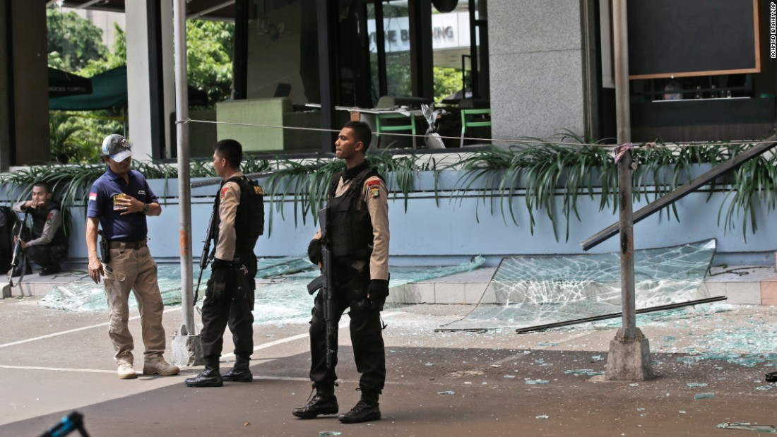 Armed police officers keep watch outside a damaged Starbucks cafe after an attack in Jakarta on January 14.
