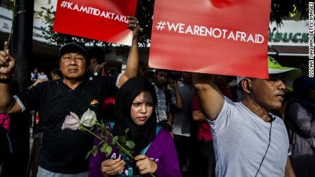 """JAKARTA, INDONESIA - JANUARY 15:  People hold placards and banners displaying the words """"we are not afraid"""" during a rally after the Jakarta terrorist attack on January 15, 2016 in Jakarta, Indonesia. Islamic State suicide bombers and gunmen struck the capital of Indonesia on January 14, killing at least two and wounding 24 during the attacks.  (Photo by Oscar Siagian/Getty Images)"""