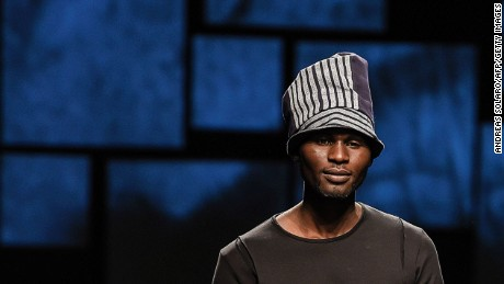 "An asylum seeker presents a creation for fashion house UMI1 during the special event ""Generation Africa"" at Pitti Immagine Uomo 89."