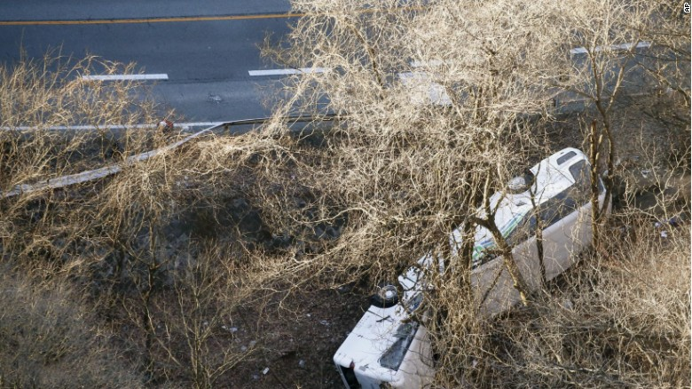 The tour bus wreckage lies off a mountain road in Karuizawa, Nagano prefecture, central Japan Friday, Jan. 15, 2016.