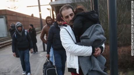 Migrants, many from Syria, walk to police vans last week in Padborg, Denmark.