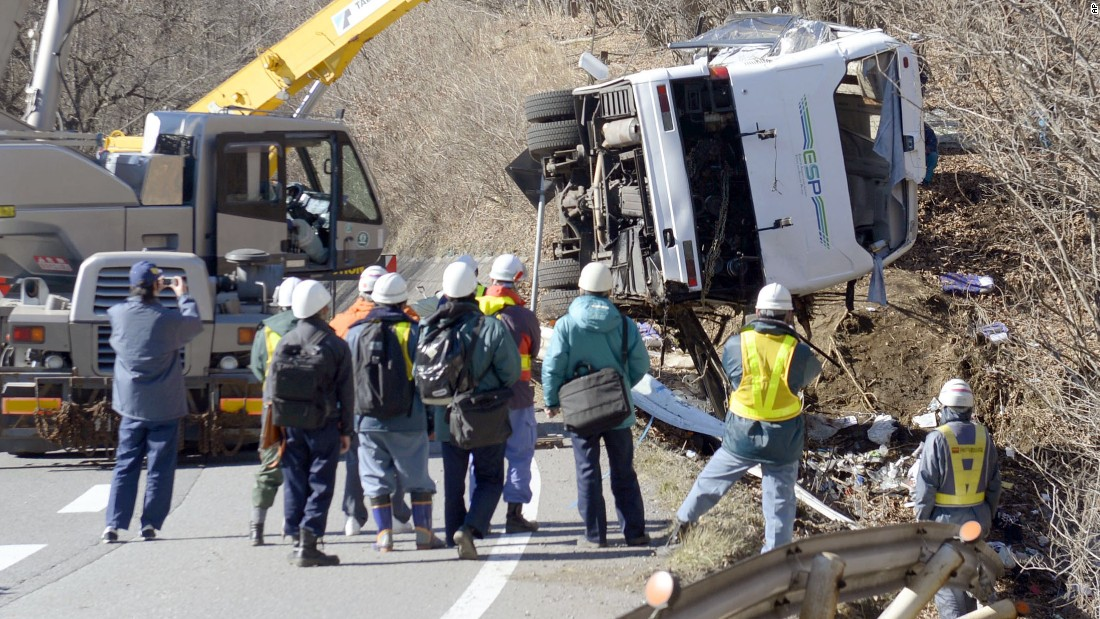 The damaged bus is lifted by crane on a mountain road in central Japan Friday, Jan. 15, 2016.