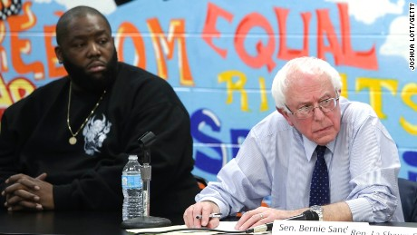 Rapper Killer Mike, left, listens as Bernie Sanders speaks during a roundtable meeting with local activist and community members December 23, 2015, in Chicago.