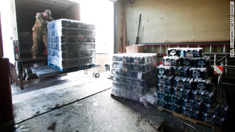 FLINT, MI - JANUARY 13:   Michigan National Guard Staff Sergeant William Phillips of Birch Run, Michigan, helps unload pallets of bottled water at a Flint Fire Station January 13, 2016 in Flint, Michigan. On Tuesday, Michigan Gov. Rick Snyder activated the National Guard to help the American Red Cross distribute water to Flint residents to help them deal with the lead contamination that is in the City of Flint's water supply.  (Photo by Bill Pugliano/Getty Images)