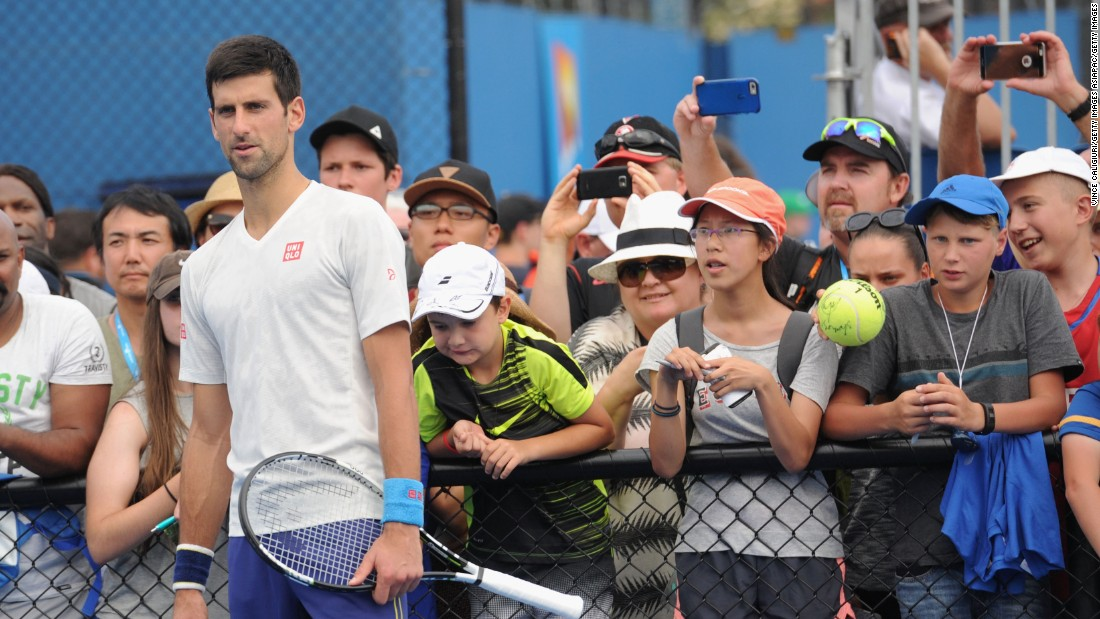 Fans get up close and personal to Novak Djokovic during a practice session at Melbourne Park.