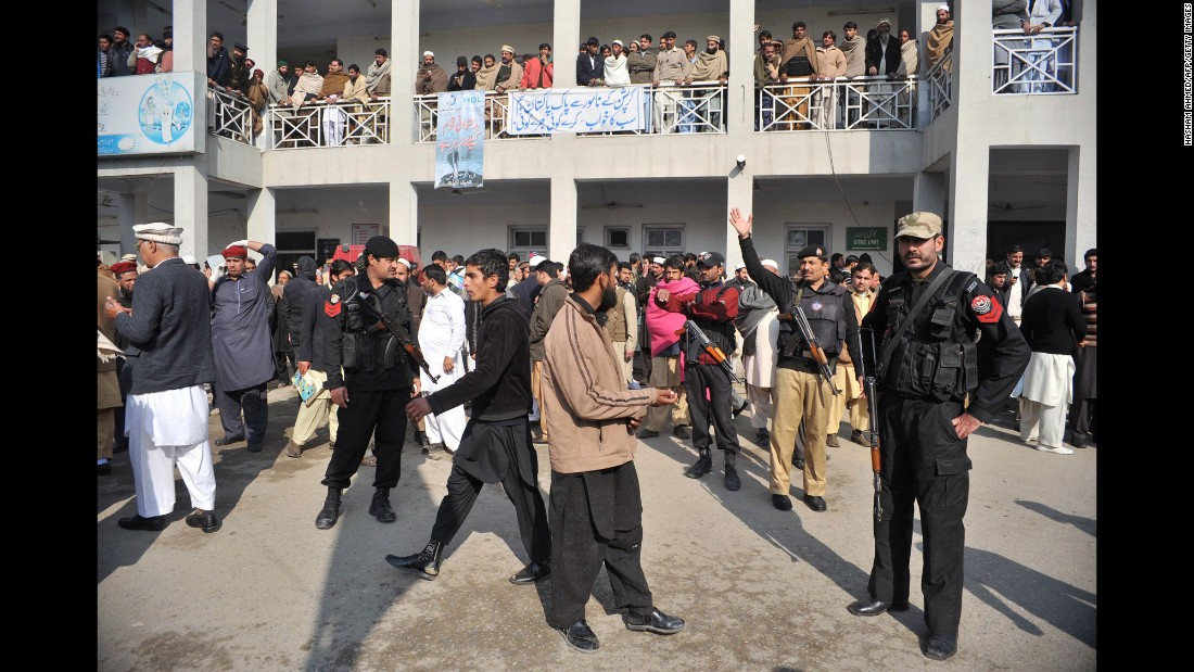 Police and onlookers gather in front of a hospital following an attack by gunmen at Bacha Khan University on January 20.