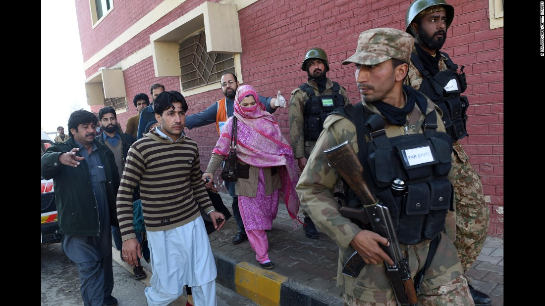 Pakistani soldiers lead people from the university.