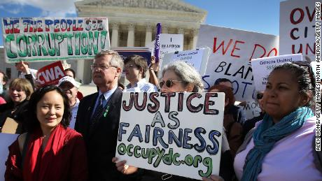 WASHINGTON, DC - FEBRUARY 23:  Annabel Park, Co-founder of the Coffee Party (2nd L) and Bob Edgar (4th L) , President and CEO of Common Cause, participate during a protest in front of the U.S. Supreme Court February 23, 2012 in Washington, DC. Activist groups Free Speech For People, the Coffee Party and Common Cause co-hosted the rally to urge the Supreme Court to overturn Citizens United v. Federal Election Commission, the decision that prohibits the government from putting limits on political spending by corporations and unions.  (Photo by Alex Wong/Getty Images)
