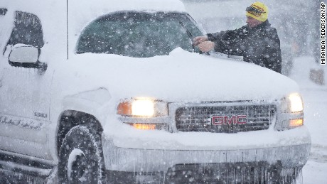 A man cleans his windshield wipers off at a stop light as snow falls, Friday morning Jan, 22, 2016, in Bowling Green, Ky. (Miranda Pederson/Daily News via AP) MANDATORY CREDIT
