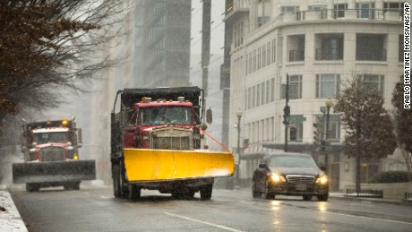 Snowplows begin to treat H Street in downtown Washington, Friday, Jan. 22, 2016. The Nation's Capital hunkers down in preparation for a major snowstorm expected to begin later today and with food and supplies vanished from store shelves, five states and the District of Columbia declared states of emergency ahead of the slow-moving system. (AP Photo/Pablo Martinez Monsivais)