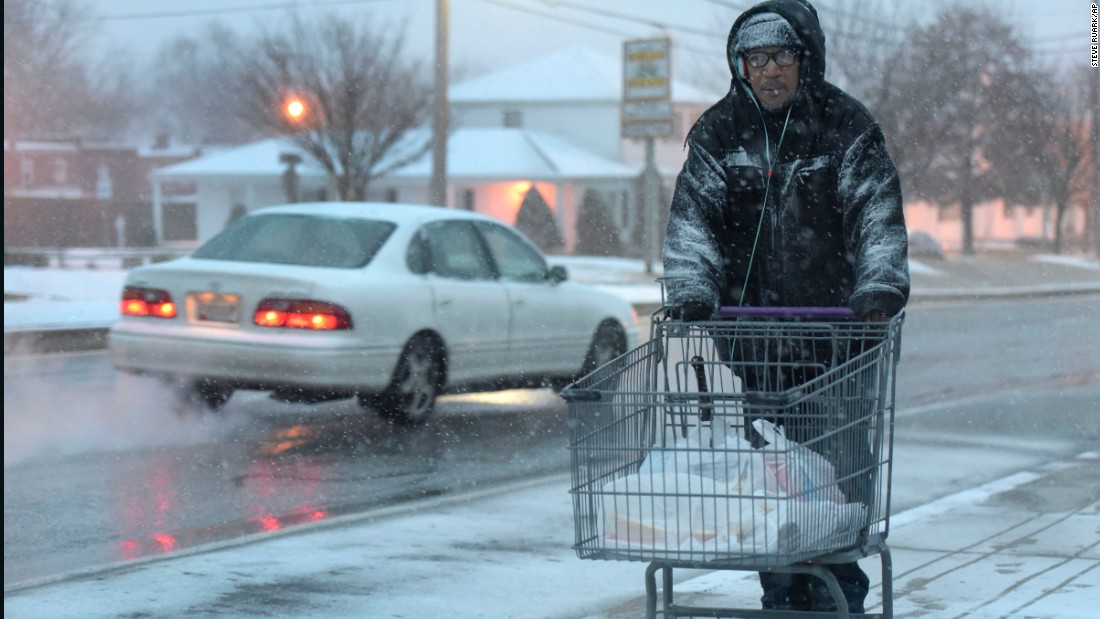 A man carts home groceries as snow falls in Towson, Maryland, on January 22.