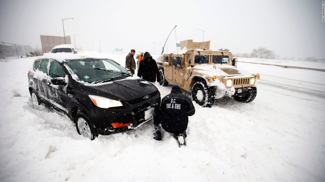 Soldiers and a Washington firefighter in a Humvee assist a stranded motorist in Washington on January 23.