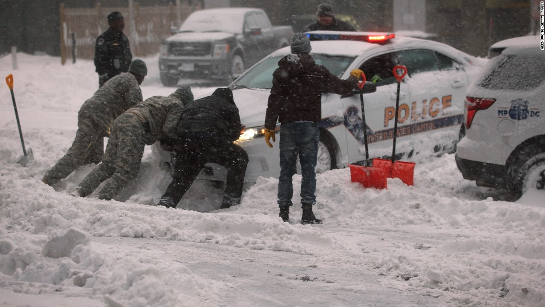 Members of the National Guard and other people help push a police car, which got stuck in the snow in Washington, D.C.