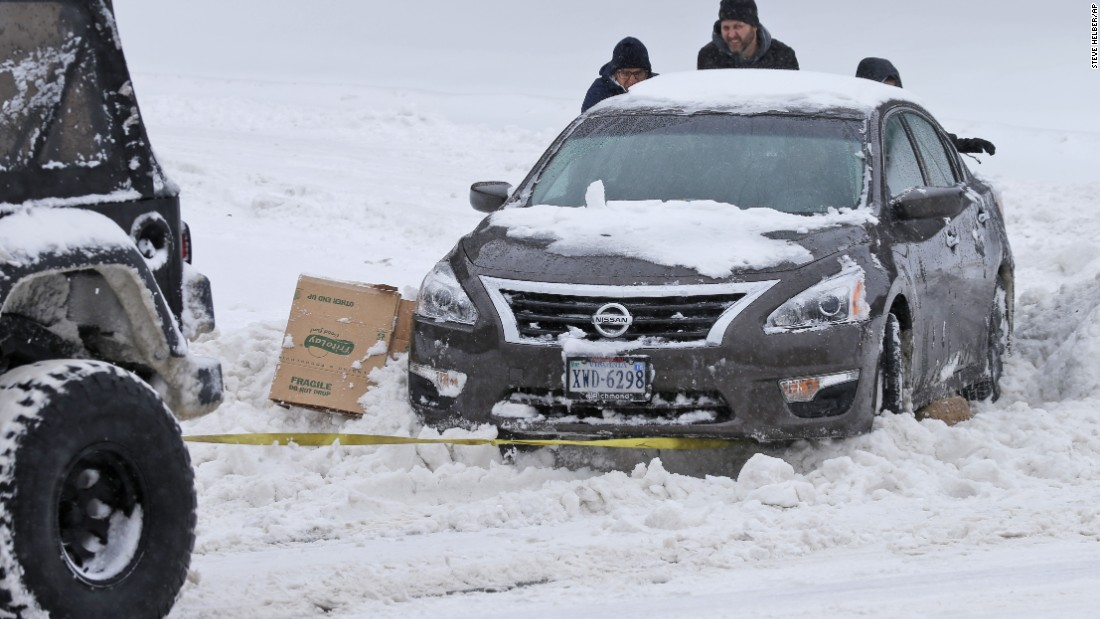 People help push a car out of the snow as another motorist tows it in Richmond on January 23.