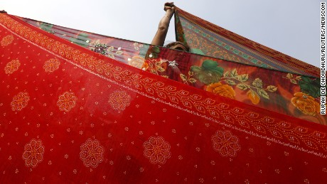 A Hindu pilgrim in Kolkata, India, dries sarees, a traditional Indian cloth used for women's clothing, after taking a dip in the waters of Ganges River during an annual trip to Sagar Island. Hindu monks and pilgrims make the trek to Sagar Island for a holy dip at the confluence of the Ganges River and the Bay of Bengal.