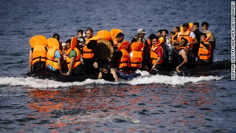 Refugees and migrants arrive on a rubber boat on the Greek island of Lesbos, after crossing the Aegean sea from Turkey, on October 18, 2015. The Greek coastguard on October 18 said five more migrants including a baby and two boys had died trying to cross the Aegean Sea from neighbouring Turkey. AFP PHOTO / DIMITAR DILKOFF        (Photo credit should read DIMITAR DILKOFF/AFP/Getty Images)