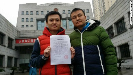 Sun Wenlin, left and his partner Hu Mingliang stand in front of the Changsha Furong District People's Court on January 5, 2016.