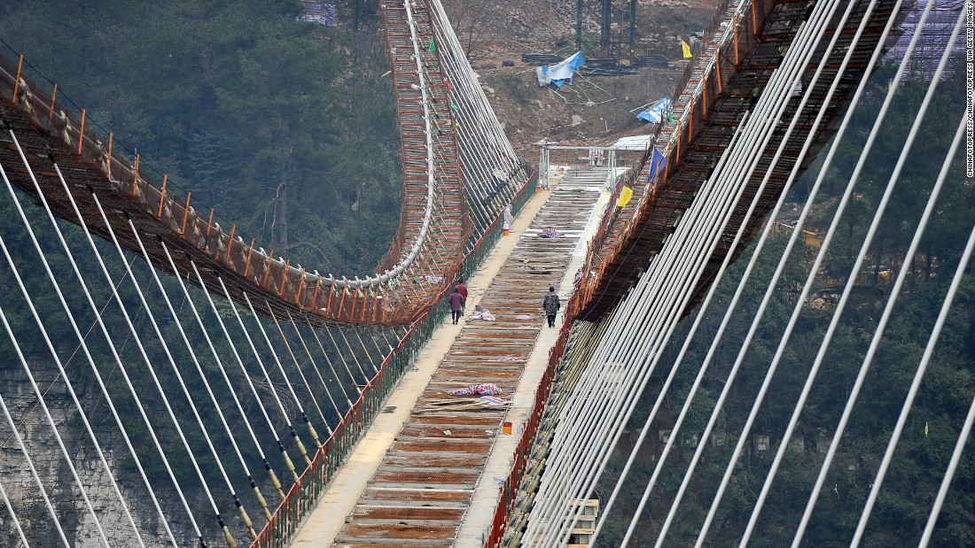 Construction workers walk along the bridge's skeletal framework. Not thrilling enough? The bridge will also reportedly feature the world's highest bungee jump.