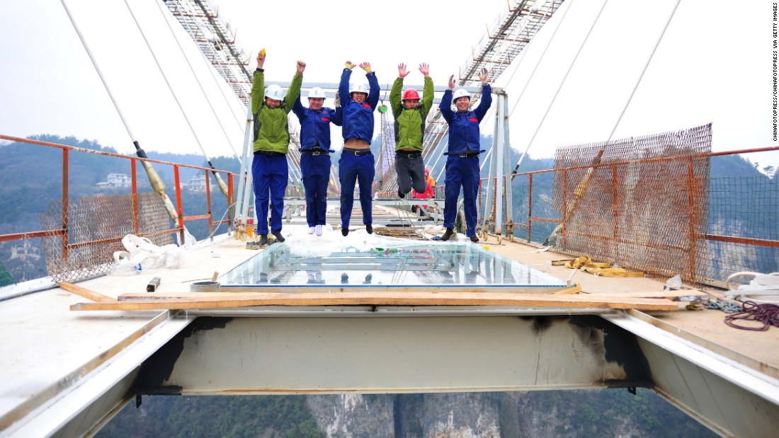 Workers installing a piece of glass on a suspension bridge do a precarious pose on January 27 in Zhangjiajie, China.