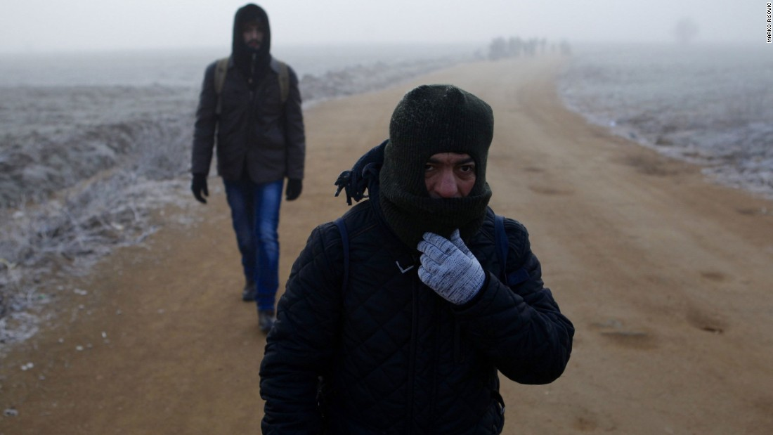 Two men from Syria walk in dense fog along a path connecting a registration center with the town of Miratovac. Because of bad weather and muddy roads, buses were waiting for them 2 kilometers (1.2 miles) from there. They were taking them to the Croatian border.