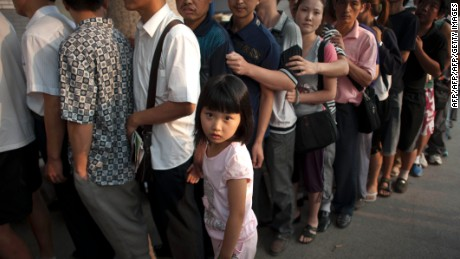 This picture taken on August 11, 2011 shows a girl standing beside her father as hundreds of Chinese parents queue up to see a doctor outside a childrens' hospital in Beijing. The BRICS group of emerging countries recently vowed to improve access to low-cost and high-quality medicine -- and called on developed nations to shoulder responsibility in helping the poor. CHINA OUT AFP PHOTO (Photo credit should read STR/AFP/Getty Images)