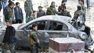 Syrian pro-government forces gather at the site of a deadly triple bombing Sunday, January 31, in the <a href=