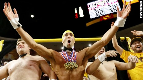 "Olympic swimmer Michael Phelps, center, performs behind the ""Curtain of Distraction"" during an Oregon State free throw against Arizona State in the second half of an NCAA college basketball game, Thursday, Jan. 28, 2016, in Tempe, Ariz. (AP Photo/Matt York)"